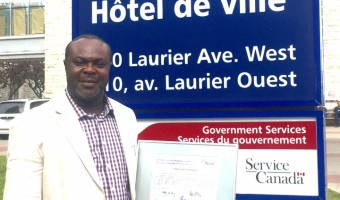 Chikezirim Nwakanma poses with award in front of City Hall