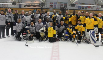The teams pose for group with Black History Ottawa President June Girvan, centre, kneeling