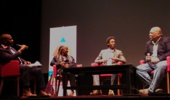 Adrian Harewood, left, moderates the panel discussion